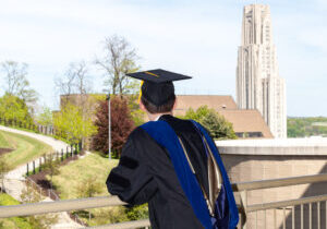 Doctoral graduate looking toward Cathedral of Learning at University of Pittsburgh