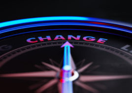 Arrow of a compass is pointing change text on the compass. Arrow, change text and the frame of compass are metallic blue in color. Red light illuminating compass is creating a sense of tension. Black backgound. Horizontal composition with copy space. Change concept.