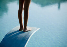 A person standing on a diving board.  Only the back of the person's legs and feet are visible.  The person is standing up straight.  There's a light reflecting off of the person's feet and the top of the board.  The diving board bends towards the water underneath the person's weight.  The diving board is light colored and blends in a little with the water.  The board is also textured with a raised border.  The water is light in color with small ripples.  Reflections of other objects in the water create a border at the top of the image.