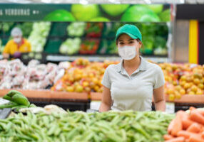 Beautiful Latin American worker at a supermarket restocking the fruits and vegetables while wearing a facemask to avoid the spread of coronavirus - pandemic lifestyle concepts