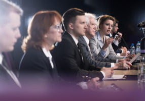 Formally dressed group of people at a conference table, with one of the women speaking to microphone