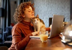 young-woman-with-cat-using-laptop-picture-id1196212232